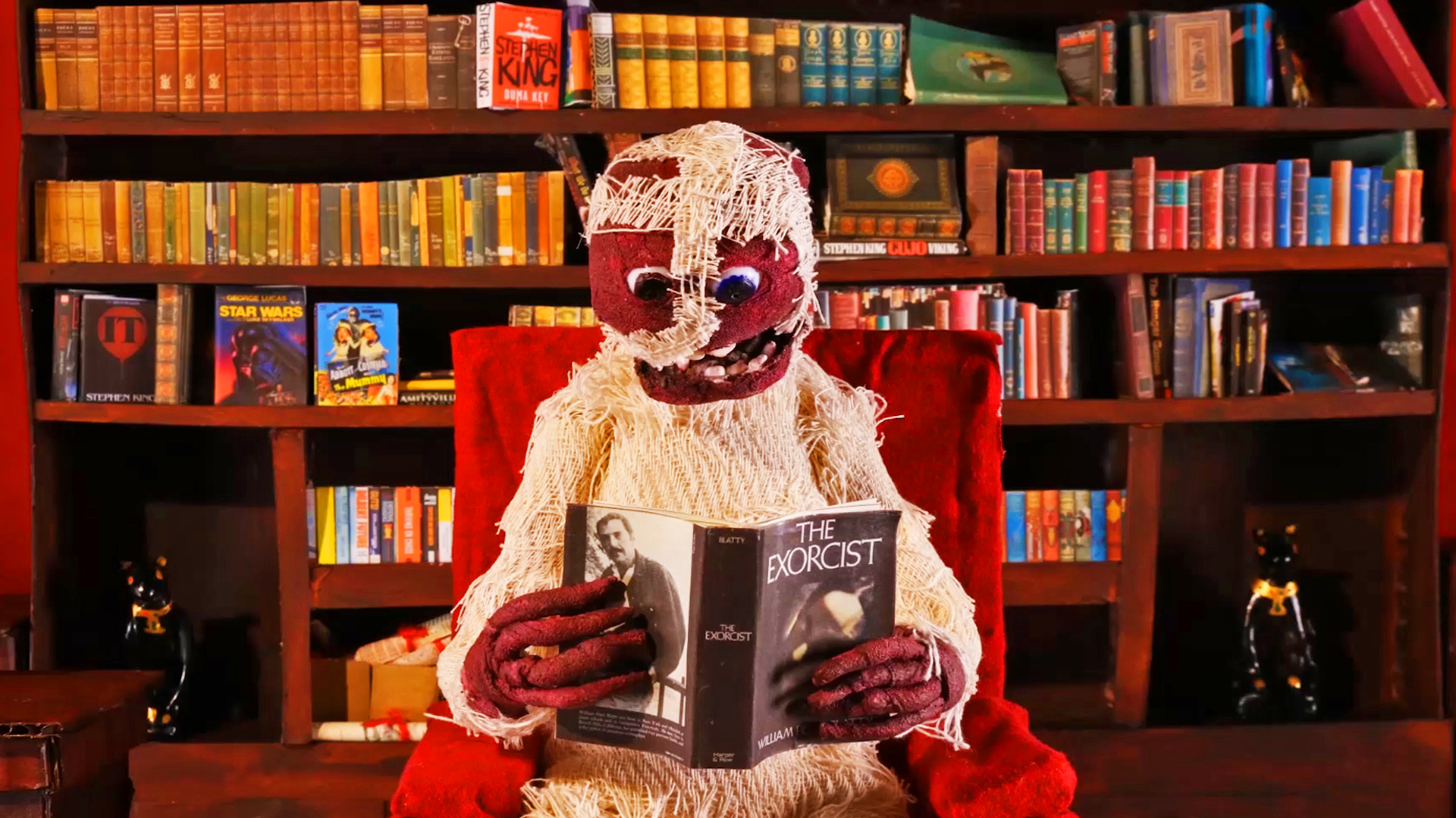 A model of a mummy reading a copy of The Exorcist