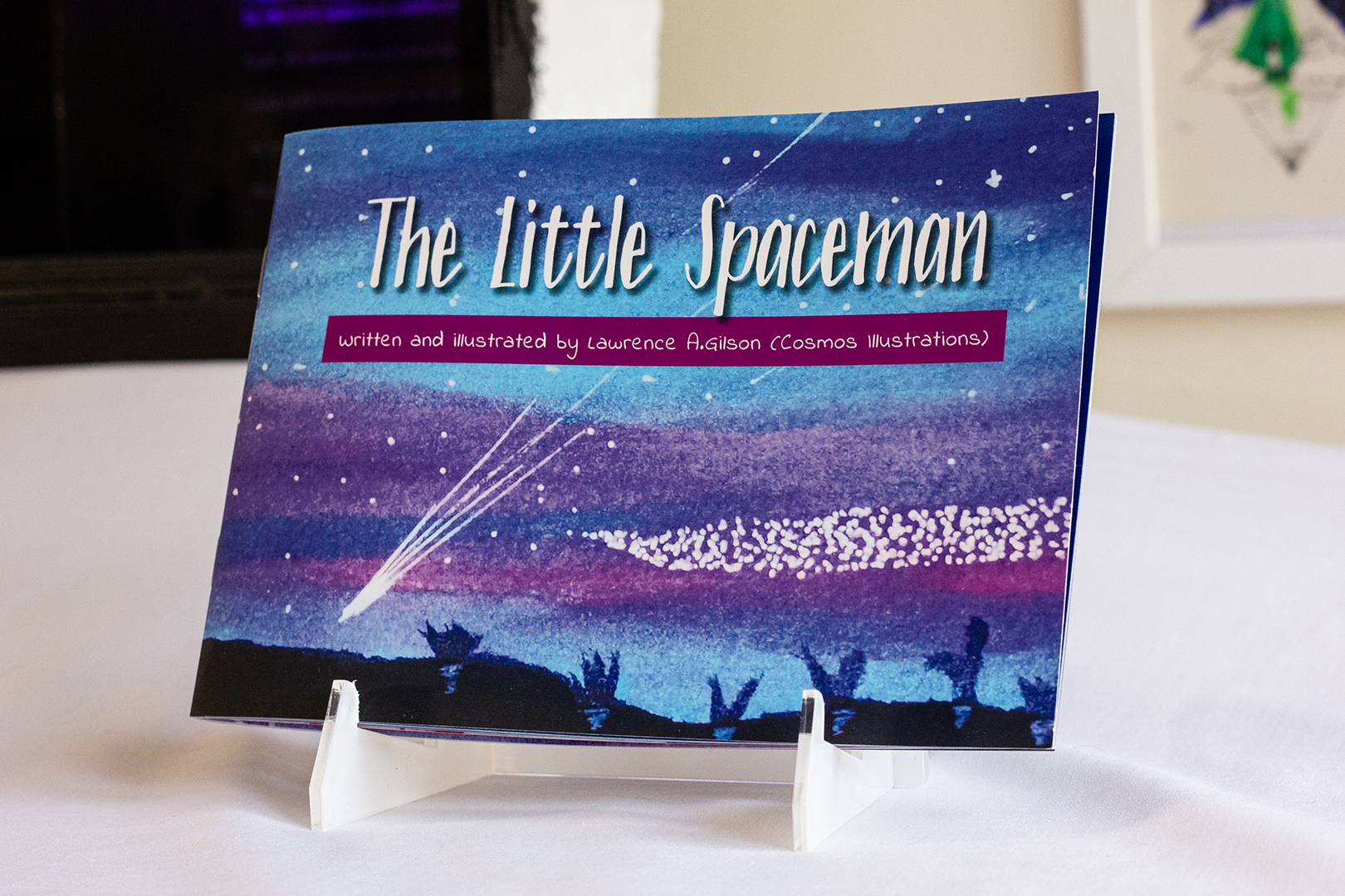 A small book called The Little Spaceman. The cover shows a cosmos with shooting stars.