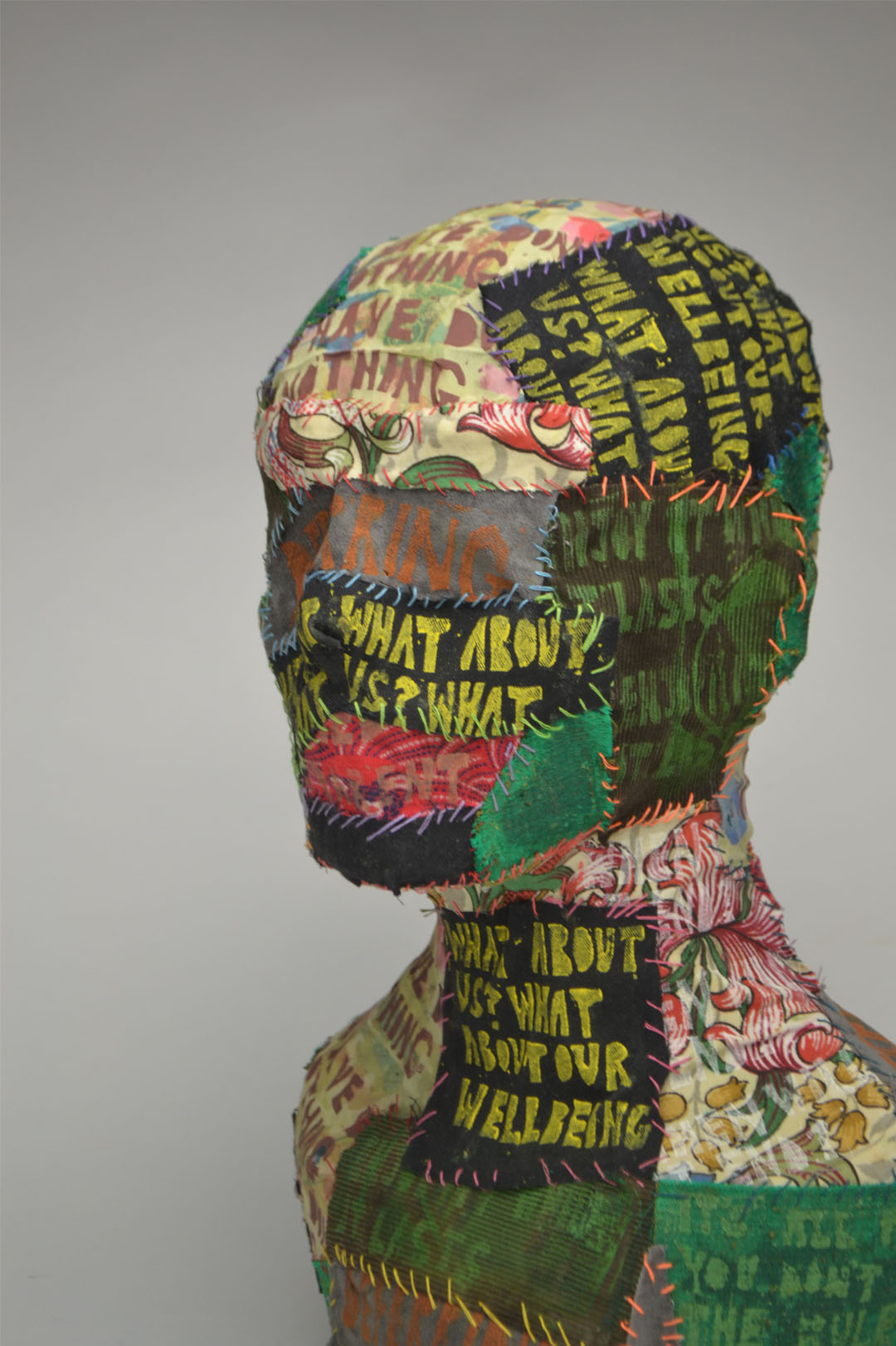 A bust covered with scraps of fabric that have been embroidered together. The fabric is printed with words and patterns.