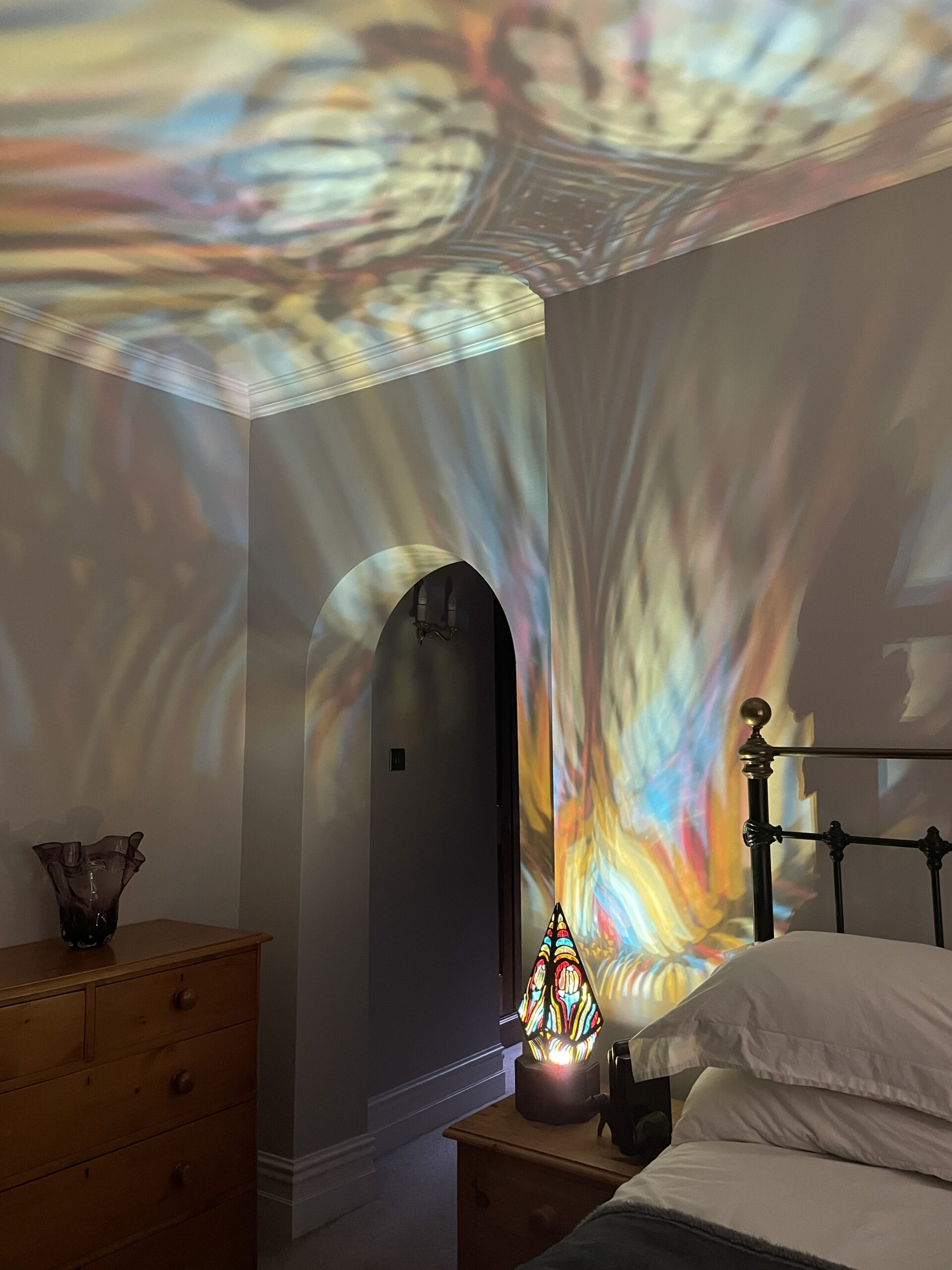 Megans lamp in a bedroom, throwing light across the wall and ceiling