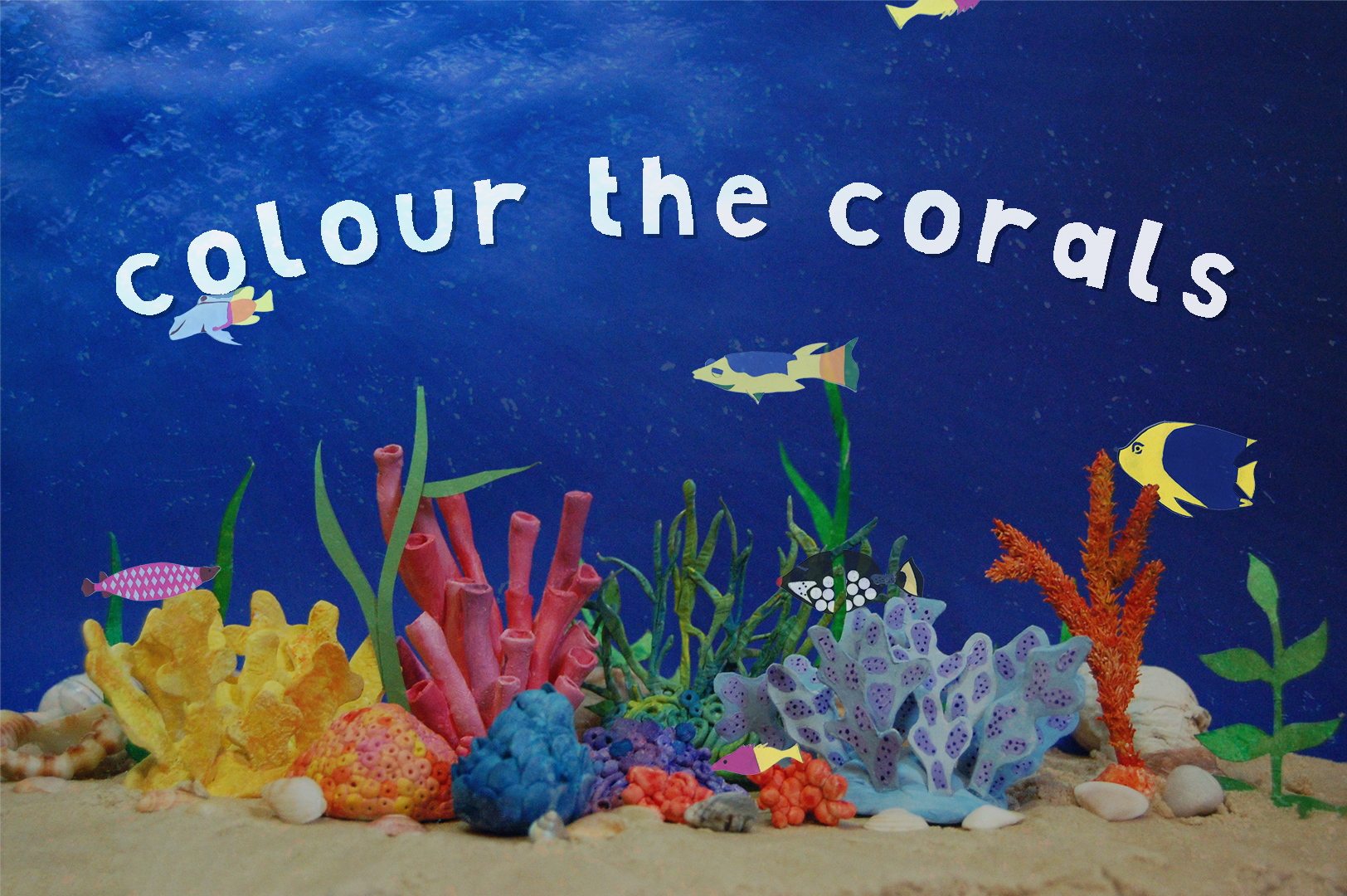 A depiction of a vibrant coral reef with paper fish swimming past. The words 'Colour the corals' are cut out in paper.