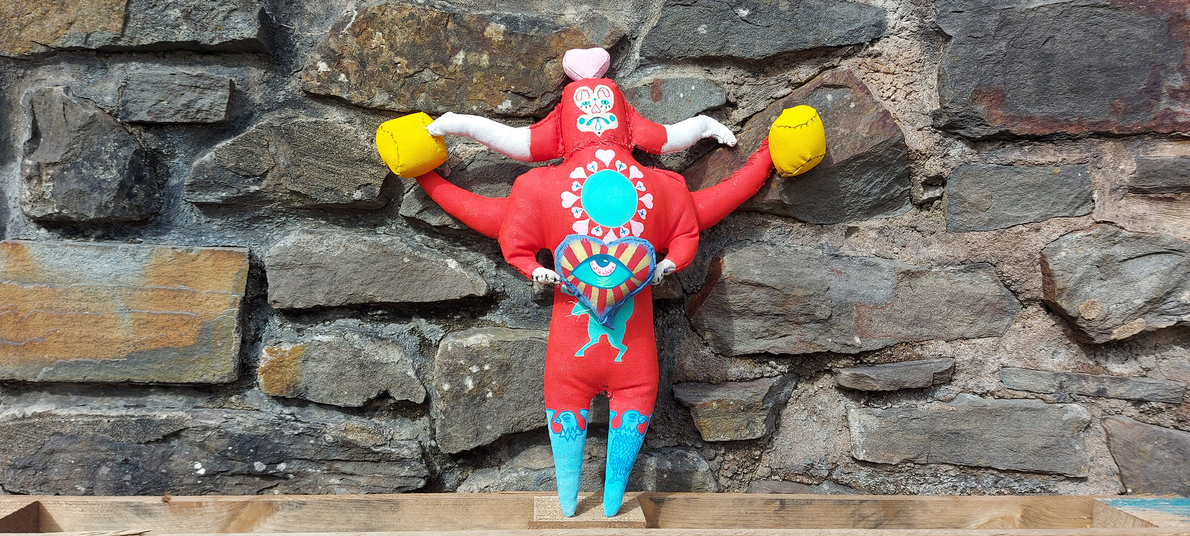A handmade doll standing in front of a brick wall. The doll is red, with horns and a pink heart on top of its head. Its face is painted with a sad clown style. Its legs have blue birds painted on them, and it holds a heart painted with a blue eye and red and yellow stripes.